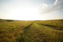 Road In A Grassy Field In The Kansas Prairie At Sunset