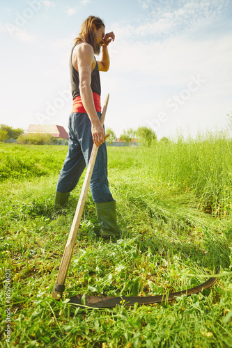 Rural farmer on summer meadow mowing grass with classic scythe Canvas-taulu