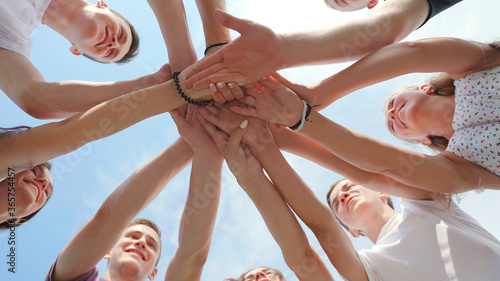 Fototapety, obrazy: Cheerful friendly friends align their hands in the center. Teamwork concept.