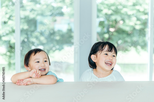 Fototapeta 爽やかな白いリビングでカウンターに座る笑顔の子ども kids house smile obraz
