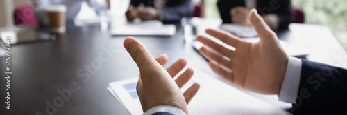 Businessman project leader gesticulate hands while talking during formal group meeting, close up Canvas-taulu