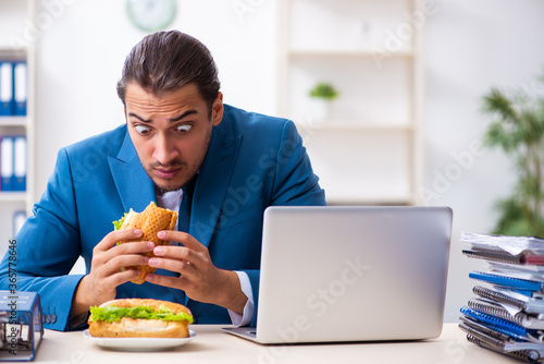 Valokuva Young male employee having breakfast at workplace