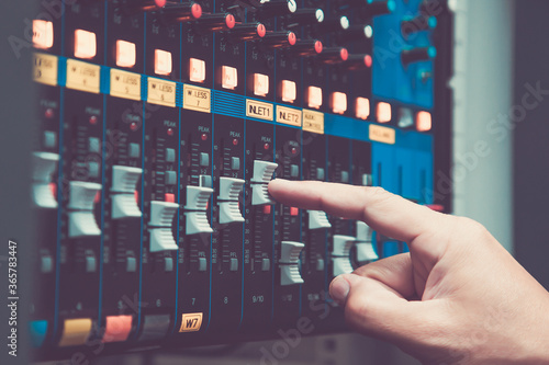 Fototapeta Close-up hand adjust the volume on sound mixer in studio workplace for live the media and sound recording equipment and sound system concept