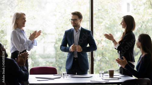 Obraz Group of diverse colleagues congratulating applauding and cheering happy businessman with business achievements, career advance, great work results, job promotion standing in modern office board room - fototapety do salonu