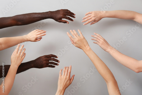 Hands of Caucasian women and African-American man on grey background Canvas-taulu