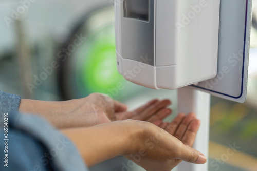 Fotografie, Obraz Close up of woman holding hands under automatic sanitiser dispense