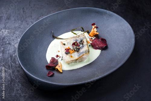 Modern style Skrei Kabeljau Fisch Filet mit Gemüse Chips und Algen in Zitonen Kokosnus Sauce angeboten als close-up auf einem Design Teller mit Textfreiraum