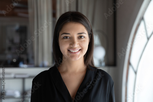 Profile picture of smiling indian young businesswoman look at camera posing at workplace, headshot portrait of happy millennial ethnic female employee show confidence, optimism, employment concept