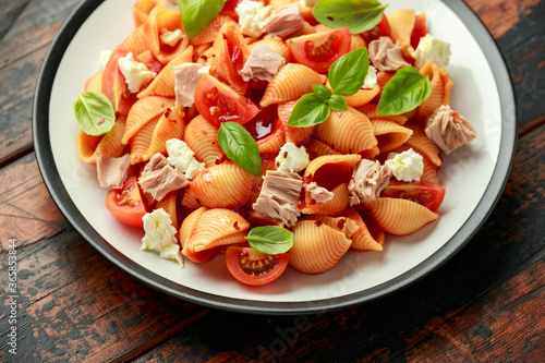 Conchiglie Tuna pasta with tomato sauce, feta cheese and basil on wooden table Fototapet