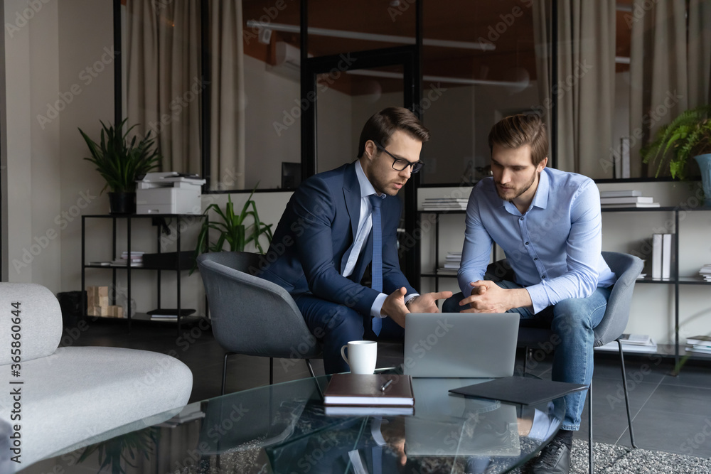 Fototapeta Serious young caucasian businessmen look at laptop screen brainstorm discuss company financial project in office together, focused male colleagues or business partners cooperate work on computer