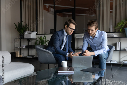 Obraz Serious young caucasian businessmen look at laptop screen brainstorm discuss company financial project in office together, focused male colleagues or business partners cooperate work on computer - fototapety do salonu