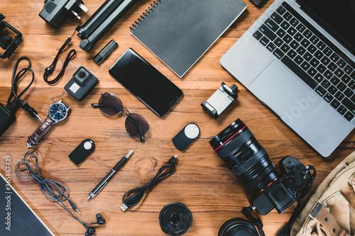 Fototapeta Top view with a digital camera, charger, camera, lens, video camera, USB, person