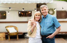 Portrait Of Mature Couple Embracing Near Their Motorhome At Campground, Copy Space