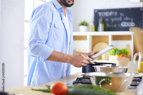 Fototapeta Man following recipe on digital tablet and cooking tasty and healthy food in kitchen at home obraz