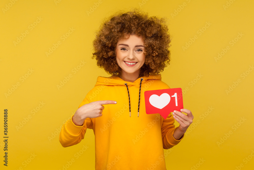 Fototapeta Internet blogging. Portrait of joyful curly-haired woman in urban style hoodie pointing at heart like icon, recommending to click on social media button. studio shot isolated on yellow background