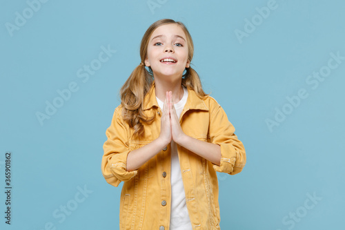 Little blonde kid girl 12-13 years old in yellow jacket posing isolated on blue background children studio portrait Canvas-taulu