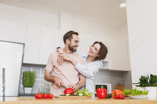 Obraz Laughing young couple two friends guy girl in casual clothes preparing vegetable salad cooking food in light kitchen at home. Dieting family healthy lifestyle concept. Mock up copy space. Hugging. - fototapety do salonu