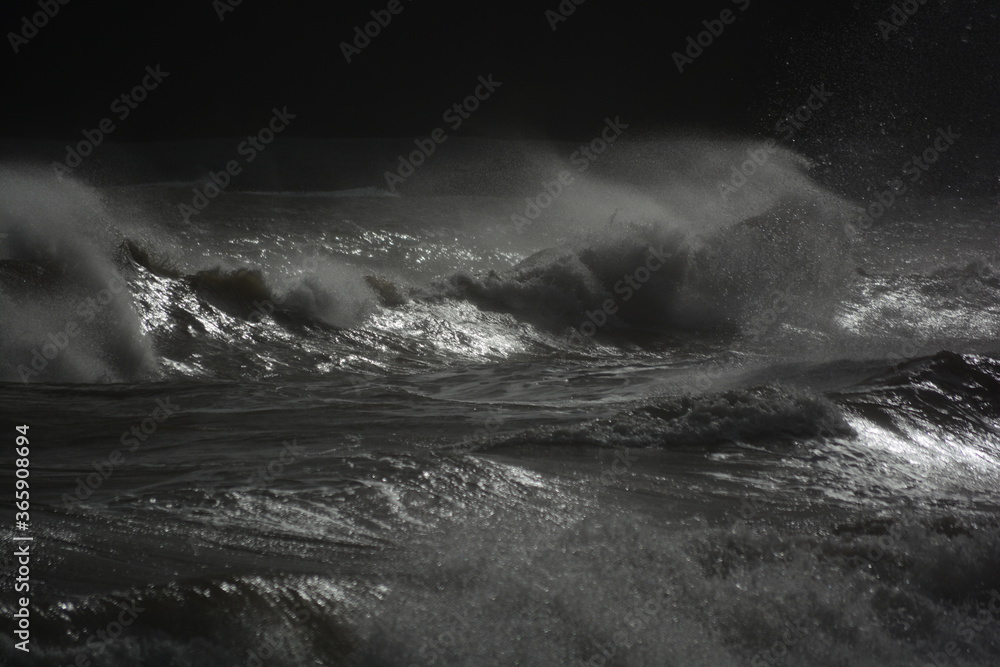 Fototapeta A stormy sea with gale force winds and the high tide creates huge waves which crash on the rocky beach. The setting sun glints across the water and the spray creates a mist across the water