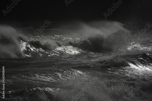 Fototapeta A stormy sea with gale force winds and the high tide creates huge waves which crash on the rocky beach. The setting sun glints across the water and the spray creates a mist across the water obraz