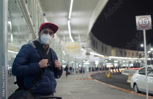 joven esperando viaje con cubrebocas en terminal de autobus aeropuerto Canvas