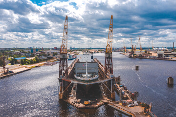 Aerial view of the city's waterfront and port infrastructure. The average dry floating dock. Big transport ship standing in docks in port in Riga, Latvia.