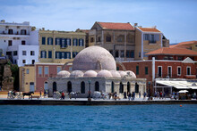 Chania, Island Of Crete, Greece - May 3, 2014. The Venetian Harbor With A View Of The Kyuchuk-Hasan Mosque( Janissary Mosque), The Embankment With People Walking And Carriages With Horses