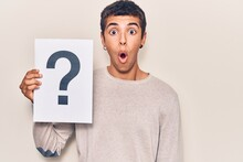 Young African Amercian Man Holding Question Mark Scared And Amazed With Open Mouth For Surprise, Disbelief Face