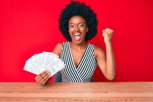 Young African American Woman Holding Dollars Screaming Proud, Celebrating Victory And Success Very Excited With Raised Arms
