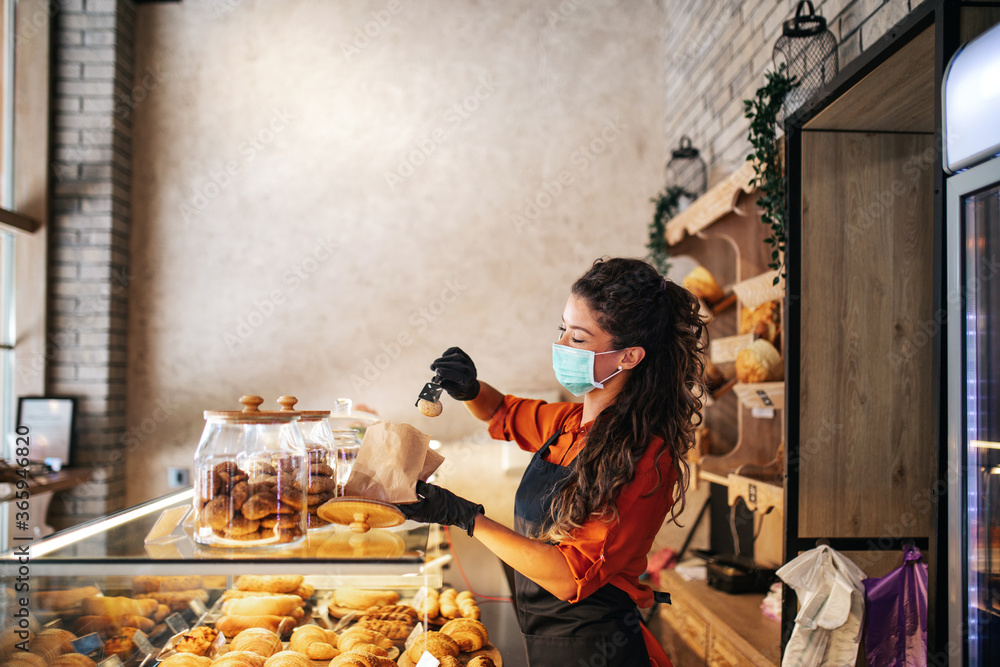 Fototapeta Beautiful young female worker with protective mask on face working in bakery.