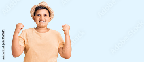 Little boy kid wearing summer hat and hawaiian swimsuit celebrating surprised and amazed for success with arms raised and open eyes. winner concept.