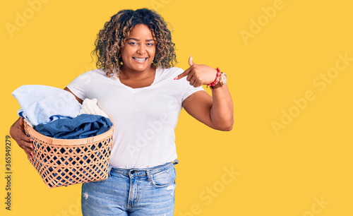 фотография Young african american plus size woman holding laundry basket pointing finger to