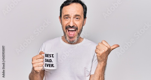 Canvas-taulu Middle age handsome man drinking cup of coffee with best dad ever message pointi