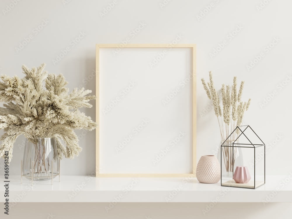 Fototapeta Wooden frame leaning on white shelf in bright interior with plants on the table with plants in pots on empty wall background.