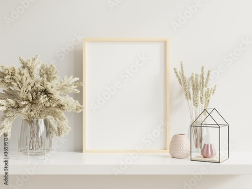 Vászonkép Wooden frame leaning on white shelf in bright interior with plants on the table with plants in pots on empty wall background