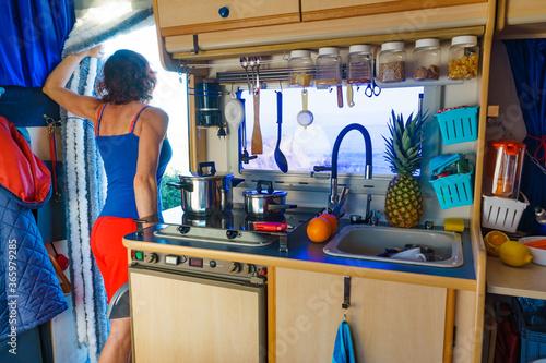 Leinwand Poster Woman inside Caravan, kitchen area