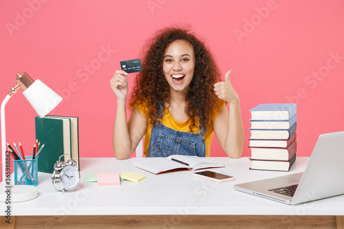 Slika na platnu Excited african american girl employee in office sit isolated on pink background