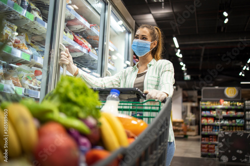 Obraz na plátně Woman with protective mask and gloves shopping in supermarket during COVID-19 pandemic or corona virus