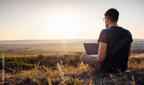 man with laptop sitting on the edge of a mountain with stunning views of the val Canvas-taulu