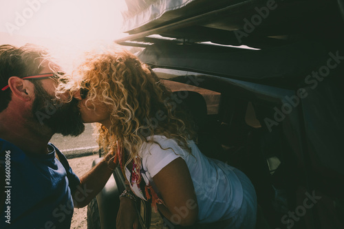 Fototapeta Adult couple in love kiss outside the car and travel together - concept of free and happy lifestyle for beautiful people traveling and enjoying life obraz