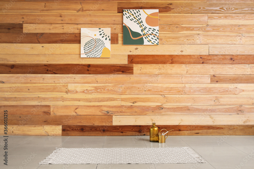 Fototapeta Vase with watering can on floor near wooden wall