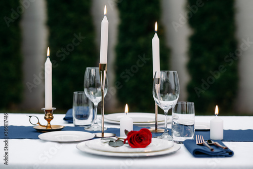 Obraz Table setting, wineglasses, candles and flower - fototapety do salonu
