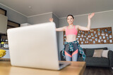 Young woman dancing at home following video lesson on the laptop. Pretty female repeating exercises while watching online workout session.