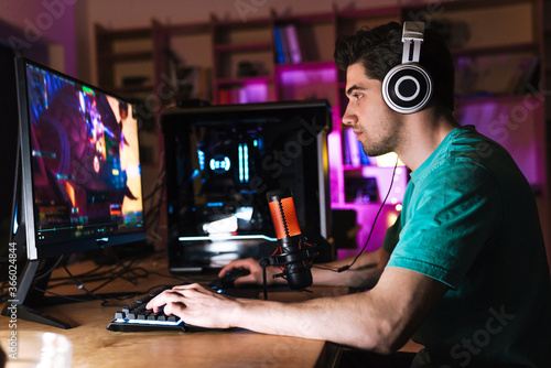 Image of caucasian focused man playing video game on computer