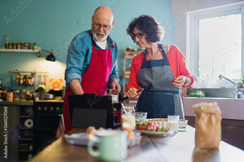 Fototapeta A cheerful couple in their fifties in their kitchen are preparing a strawberry tart. They are looking for the recipe on a digital tablet obraz