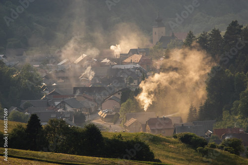 Fototapeta  mountain village in the valley suffocating with smoke and smog from wood and coal-fired stoves obraz
