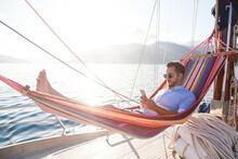 Man Relaxing On Yacht In Hammock. Traveler With Mobile Phone. Travel On Sailboat. Summer Vacation In Self Isolation, Social Distance. Freelancer Workplace In Quarantine. Successful Business Lifestyle.
