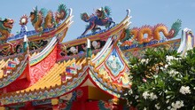Traditional Oriental Taoist Chinese Monastery Temple Roof Details, Festive Dragon Decoration. Classic Asian Religious Multicolor Shrine Or Pagoda In Bloom Of Plumeria Frangipani Flowers On Sunny Day