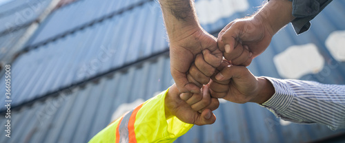 Unity and success concept.Bottom view of Engineer team people standing hands holding together at the container yard.Low Angle View of worker and businessman Team Stacking Hands.Panoramic banner.