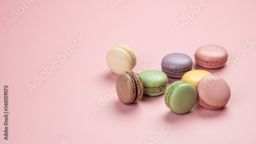Slika na platnu Closeup shot of colorful macaroons of different flavors on a pink background