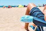 Fototapeta Kawa jest smaczna - mask and man sitting in a deck chair on the beach